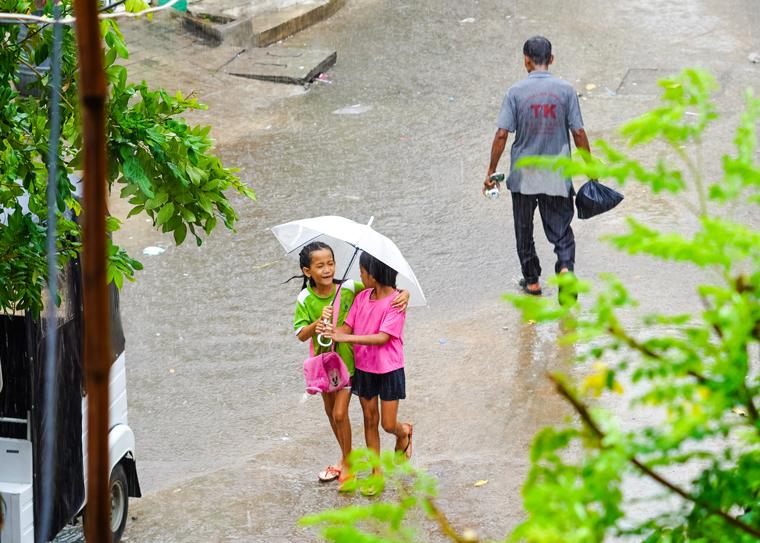 young girls share umbrella in cambodia